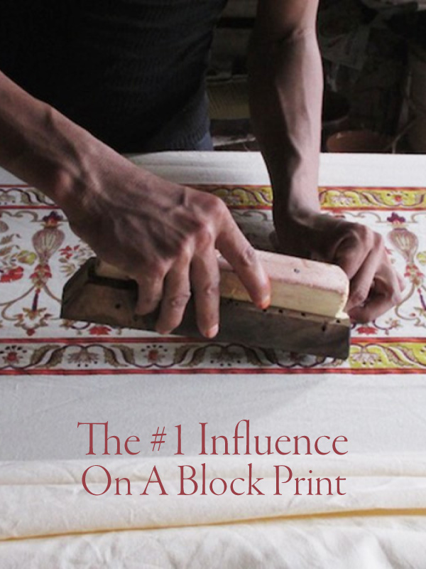 """Hands stamping a wood block print with a sign that says """"The #1 Influence On A Block Print"""""""