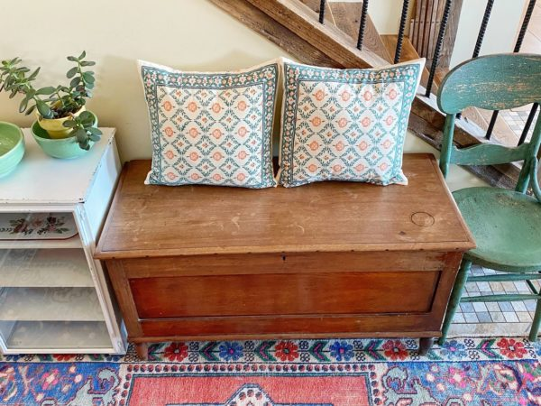 two throw pillows in an Indian print on an entry bench surrounded by eclectic decor