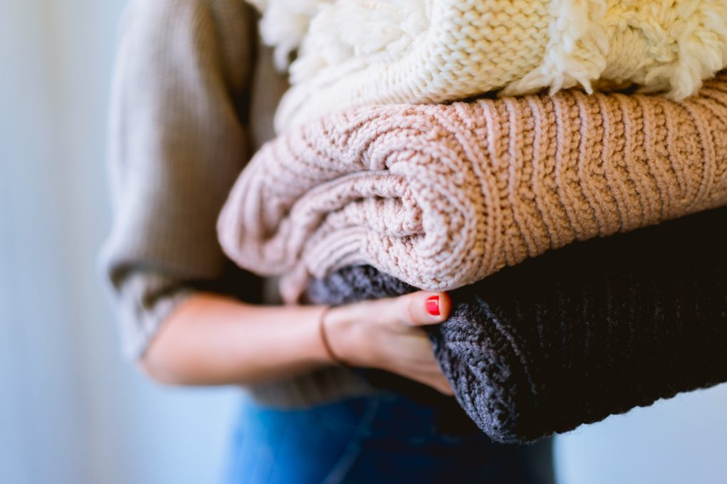 woman carrying stack of fresh blankets