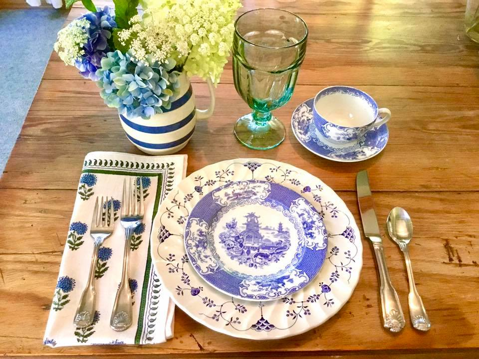 place setting with cottage style china, flowers, cloth napkins