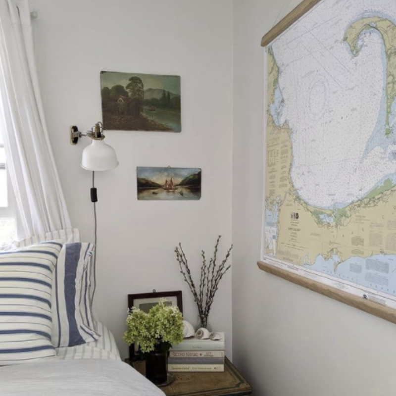 white walls, striped pillows, map and nautical art in a coastal bedroom