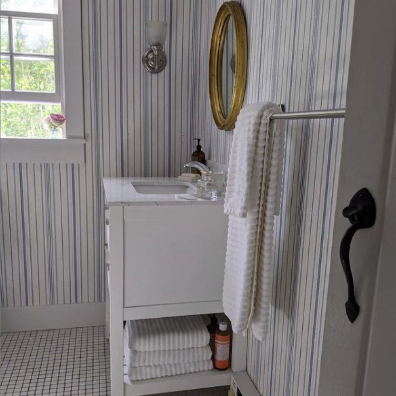 striped wallpaper in coastal bathroom with brass mirror, sconce, and window open, white towels