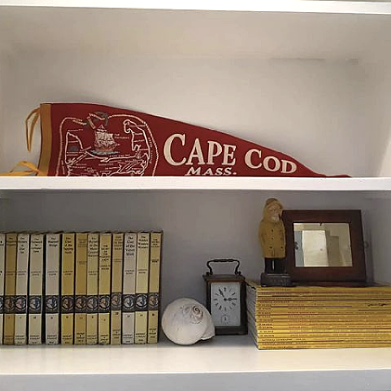 Bookcase styled with shell, Cape Cod pennant, and books