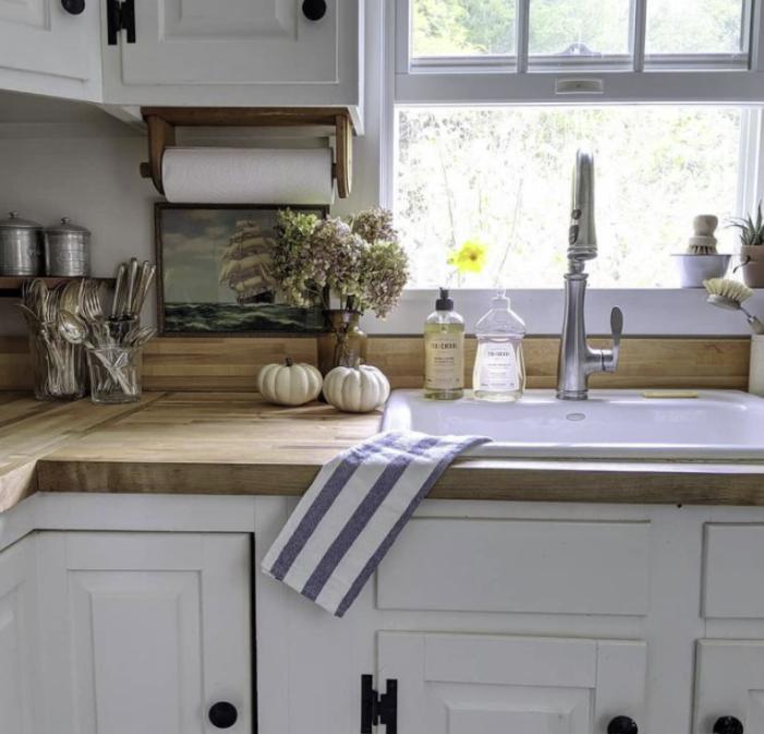 White kitchen, wood counters, white pumpkins, striped towel