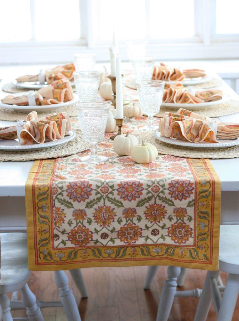 orange table runner and cloth napkins, white pumpkins