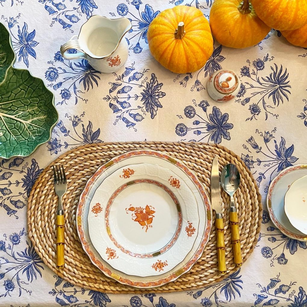 blue and white floral tablecloth and orange pumpkins
