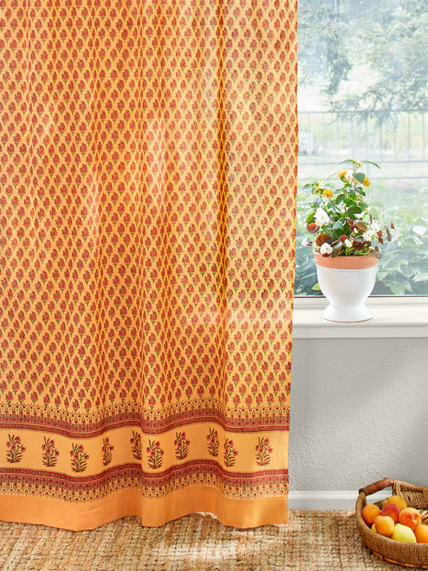 an orange shower curtain with a small red floral pattern and a red floral motif at the border