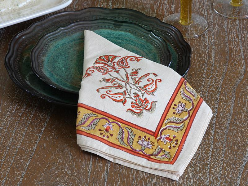 cloth napkin with floral pattern folded over green plate