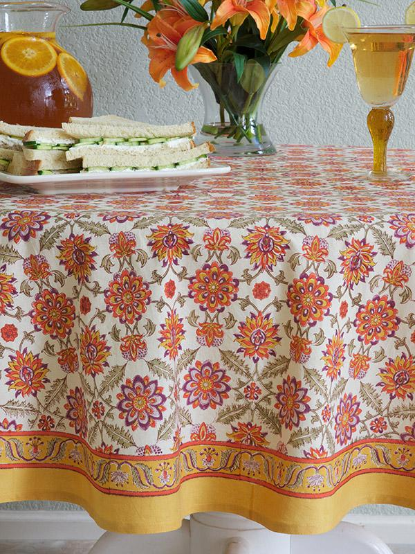 floral pattern orange tablecloth with iced tea and sandwiches
