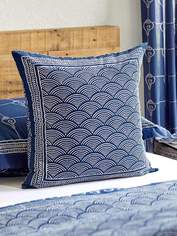 navy blue decor in a bedroom dressed in a navy blue bedspread and coastal navy blue pillow with creamy wave pattern