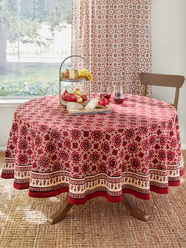 red kilim print table linens with fruit, wine, and cheese