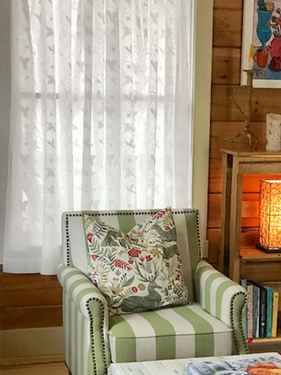 cottage style living room with white sheer curtains and wood paneling