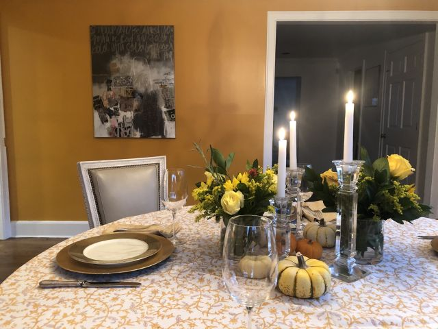 yellow Thanksgiving tablecloth, candles and gourds